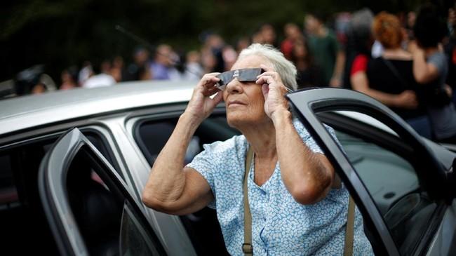 <p>Ternyata ada banyak cara unik untuk menikmati gerhana dengan aman. Tak cuma menggunakan kacamata gerhana seperti dilakukan nenek ini.</p>