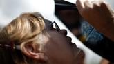 <p>Cara aman lain adalah dengan mengintip dari balik lembaran X-ray. Perempuan ini menyaksikan gerhana sebagian dari Institut Penelitian Sains Venezuela di San Antonio de los Altos, Venezuela.</p>