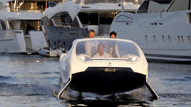 Tim SeaBubbles yang terdiri dari founderdan presiden Anders Bringdal (tengah), deputy managing directorCamille Therond-Charles, dan VP serta founderAlain Thebault menjajal purwarupa taksi air di pelabuhan Saint-Tropez, Prancis. (REUTERS/Philippe Laurenson)