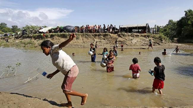Sebagian dari mereka terdampar di tanah tak bertuan yang memisahkan kedua negara. Sebagian lainnya terpaksa menyeberangi sungai untuk menuju ke Bangladesh. (Reuters/Mohammad Ponir Hossain)
