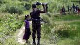 Ribuan warga minoritas Muslim Rohingya di Myanmar melarikan diri dari Rakhine ke arah Bangladesh dan disambut oleh petugas perbatasan. (Reuters/Mohammad Ponir Hossain)