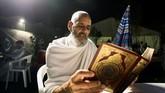 Seorang jemaah di Jabal al-Rahmah membaca kitab suci Al-Quran. Hari Arafah adalah hari ke-9 dalam bulan Dzulhijjah dan merupakan hari ke-2 dalam ritual ibadah haji. (AFP PHOTO / BANDAR ALDANDANI)