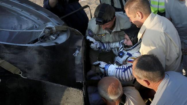 Tim di darat berupaya membantu astronaut keluar dari kapsul yang membawa mereka kembali ke Bumi. (REUTERS/Sergei Ilnitsky/Pool)