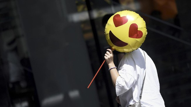 Seorang perempuan memegang balon ketika melewati toko di hari Valentine di China pada 28 Agustus 2017. Biasanya para perempuan menunjukkan kemampuan mereka serta berharap mendapatkan suami yang baik ketika festival Qixi atau festival Valentine di China tiba. (AFP PHOTO / WANG Zhao)
