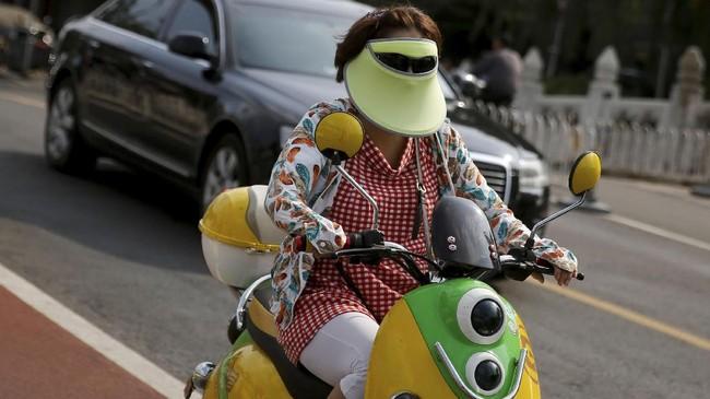Seorang wanita menggunakan pelindung muka dan kacamata hitam untuk melindungi diri dari matahari, sembari menggendarai skuter di Beijing, China, 14 Agustus 2017. (REUTERS/Thomas Peter)