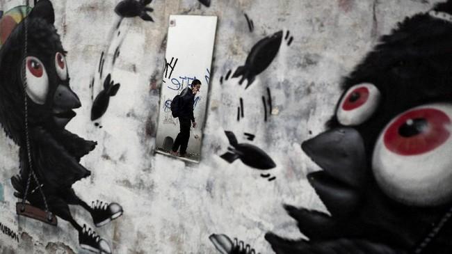Cerminan seorang pria yang sedang menggunakan telepon pintarnya di Bangkok, Thailand, 9 Agustus 2017. (REUTERS/Athit Perawongmetha)