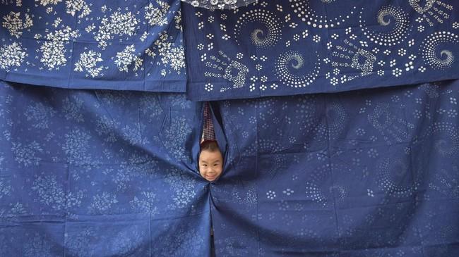 Seorang bocah bermain di pusat kerajinan kain di Shaoyang, Provinsi Hunan, China pada 18 Juli 2017. (REUTERS/Stringer)
