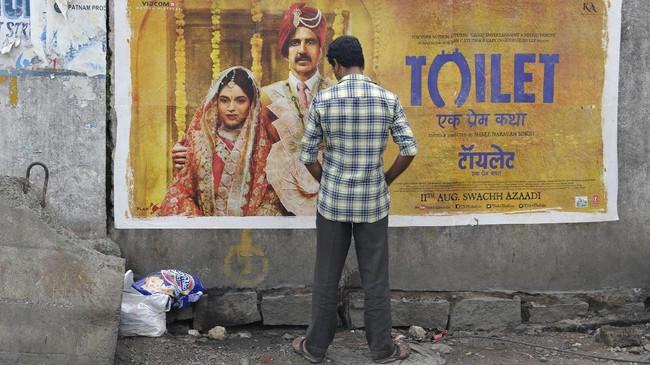 Seorang pria India membuang air kecil di depan poster film berjudul