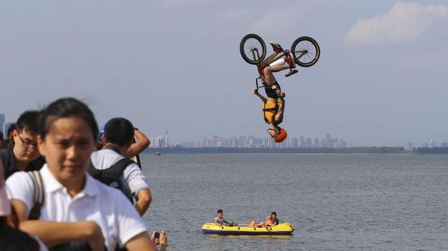 Seorang pria menunjukkan trik-trik menggunakan sepeda BMX. Ia melompat ke Danau Timur di Wuhan, Provinsi Hubei, China, pada 19 Agustus 2017. (REUTERS/Stringer)