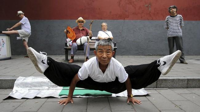 Seorang pria melakukan split ketika berlatih Kung Fu di Taman Beihai di Beijing China, 20 Agustus 2017. (REUTERS/Stringer)