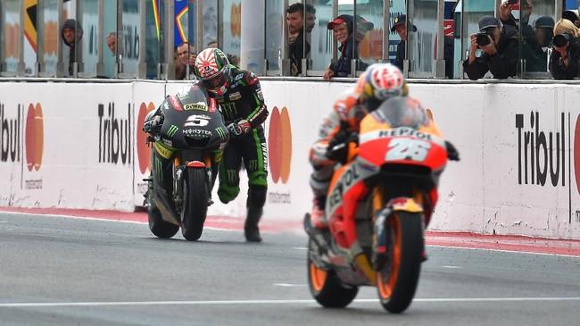 Pebalap Tech 3 Yamaha Johann Zarco berhasil meraih satu poin setelah mendorong sepeda motornya melewati garis finis. Motor yang ditunggangi Zarco mengalami kehabisan bahan bakar. (AFP PHOTO / ANDREAS SOLARO)