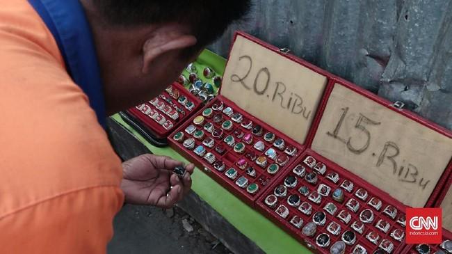 <p>Hilangnya musim batu akik di tahun 2017 tidak menyurutkan semangat para pedagang yang berjualan di emperan toko pasar Jatinegara. Pedagang menyiasati dagangan dengan batu imitasi atau batu yang mempunyai kadar campuran plastik dan batu asli. Harga jualnya pun terbilang murah berkisar Rp15 ribu hingga Rp30 ribu. (CNN Indonesia/Andry Novelino)</p>