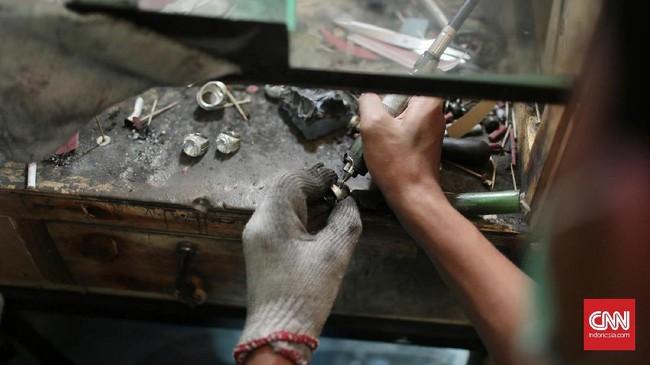 <p>Seniman cincin Perak sedang menyepuh cincin pesanan pelanggan. Sebagian pedagang, seniman batu dan cincin yang tersisa kini terus berusaha untuk mendapatkan keuntungan dari usaha mereka di Jakarta Gems Center, Rawa Bening. (CNN Indonesia/Andry Novelino)</p>