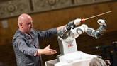 Konduktor asal Italia, Andrea Colombini dan robot komposer 'Yumi' saat persiapan konser The Lucca Philharmonic Orchestra di The Teatro Verdi di Kota Pisa, Italia.
