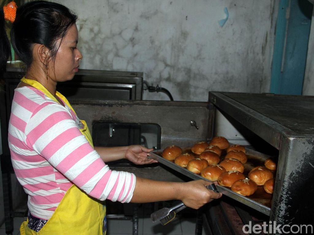 Seorang pegawai Orchid Bakery sedang membuat roti.
