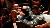 Robot ini merupakan dua tangan mekanis yang memandu para pemain orkestra.