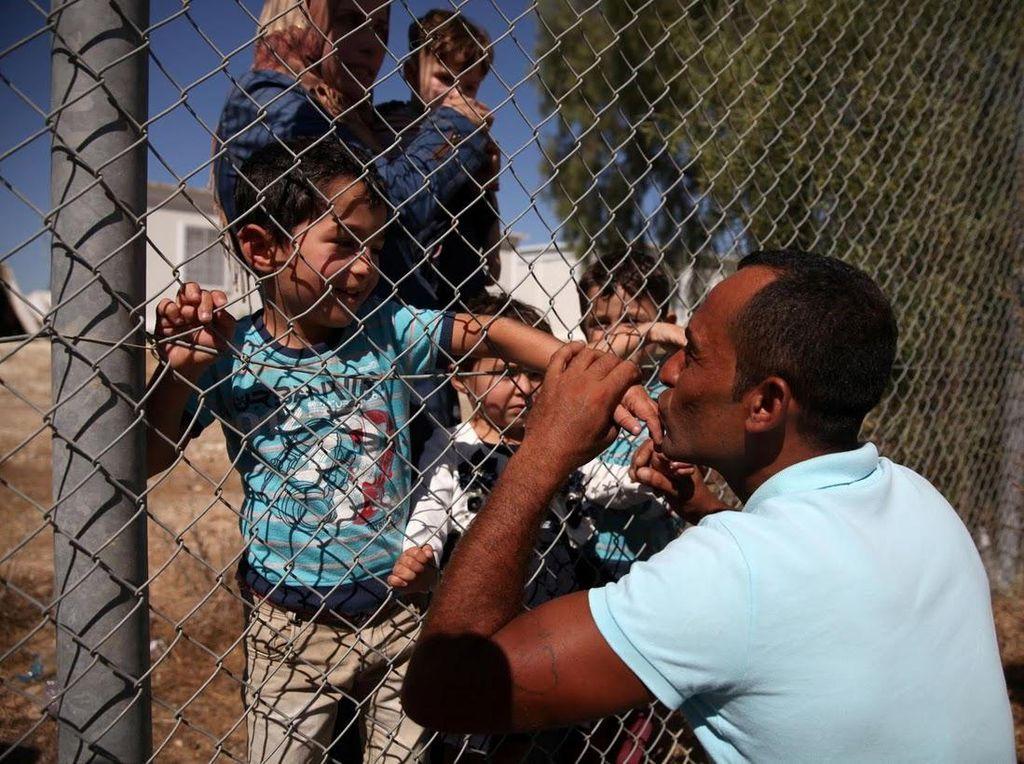 Pengungsi Suriah Ammar Hammasho tak sanggup menahan rindu saat bertemu kembali dengan keluarganya di Siprus. Reuni dengan istri dan keempat anaknya itu masih dibatasi oleh pagar kawat (Foto: REUTERS/Yiannis Kourtoglou)