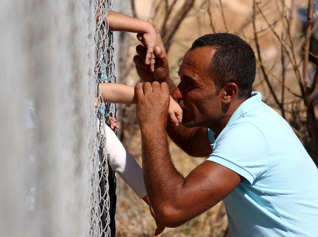 Sambil berlutut, Ammar Hammasho mencium satu persatu anak laki-lakinya dengan dibatasi pagar setinggi 3 meter. (Foto: REUTERS/Yiannis Kourtoglou)