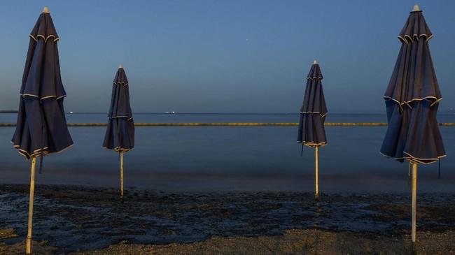 <p>Minyak tumpah dari kapal karam di Yunani menyebardan menodaisejumlah pantai-pantai terkemuka di Yunani dengan warna hitam pekat. (AFP Photo/Angelos Tzortzinis)</p>