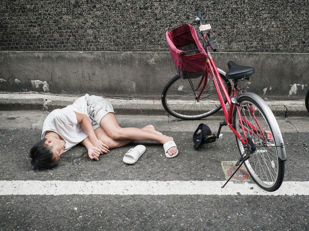 Gimana ya rasanya tidur di atas jalan dengan pakaian seadanya? Pria ini tampaknya sudah benar-benar mabuk. Sampai sendalnya masih terpakai sebelah. Foto: Lee Chapman