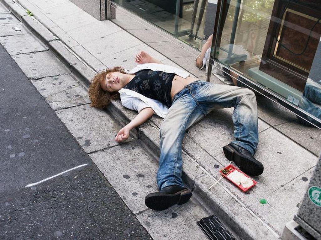 Mungkin saat mabuk, pria ini masih makan. Sampai makanannya tergeletak di samping kakinya. Foto: Lee Chapman