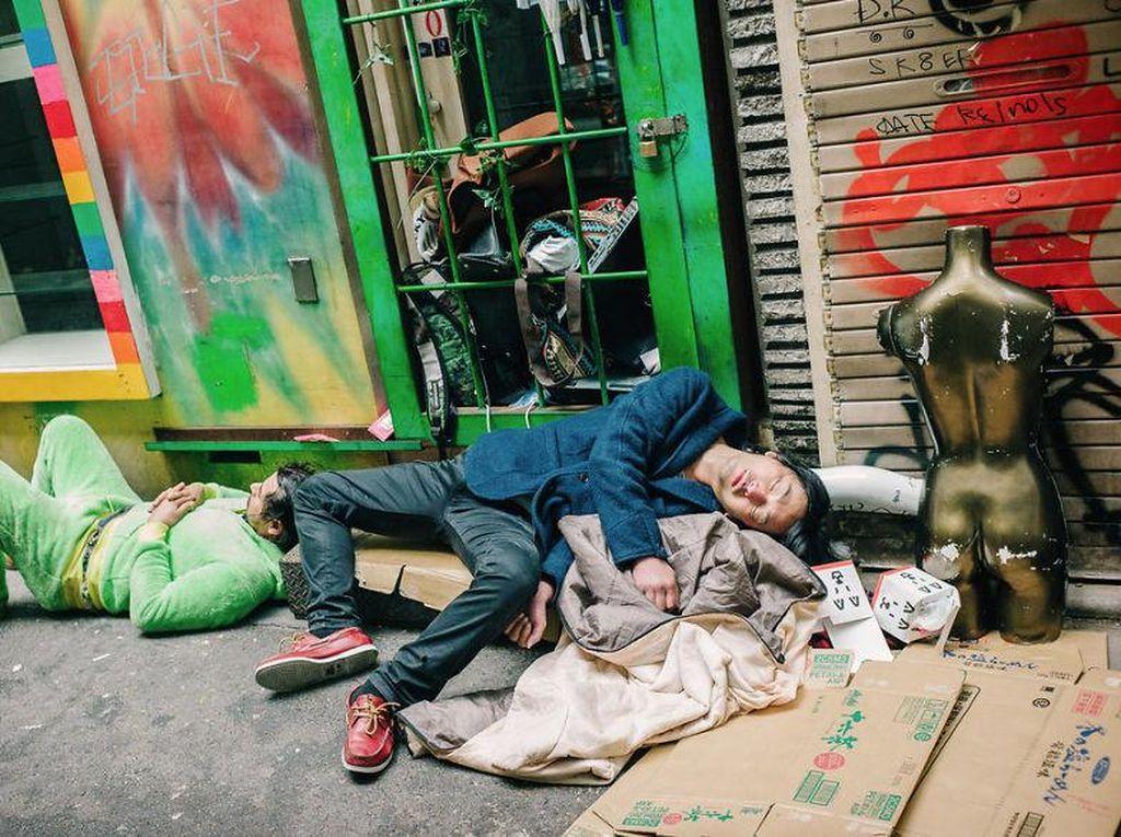 Pakaian pria ini terlihat rapi. Tapi malah tidur di atas tumpukan kardus. Memang sebaiknya sadari batas minum alkohol. Foto: Lee Chapman
