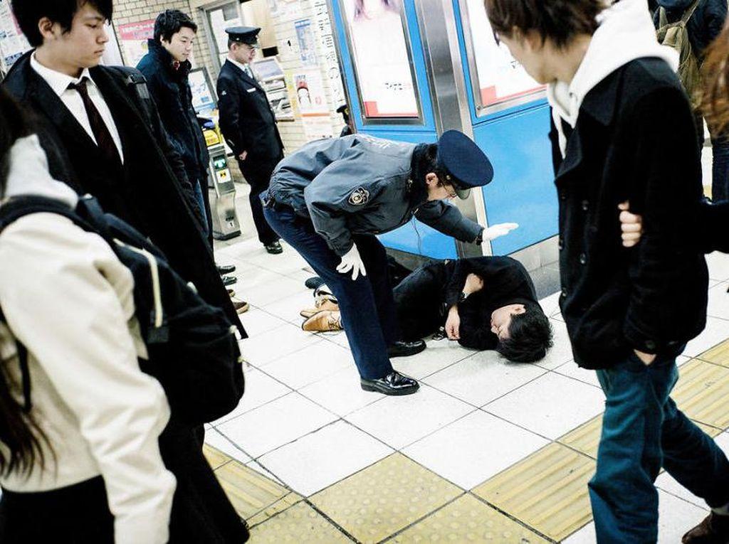 Nah kalau yang ini mabuk sampai ketiduran di stasiun. Petugas pun ikut turun tangan. Foto: Lee Chapman