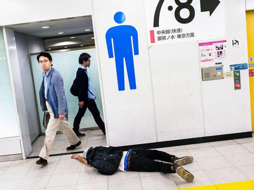 Mungkin awalnya pria ini mau ke toilet, walau sedang mabuk. Duh, bisa-bisa tangannya terinjak orang yang lalu lalang. Foto: Lee Chapman