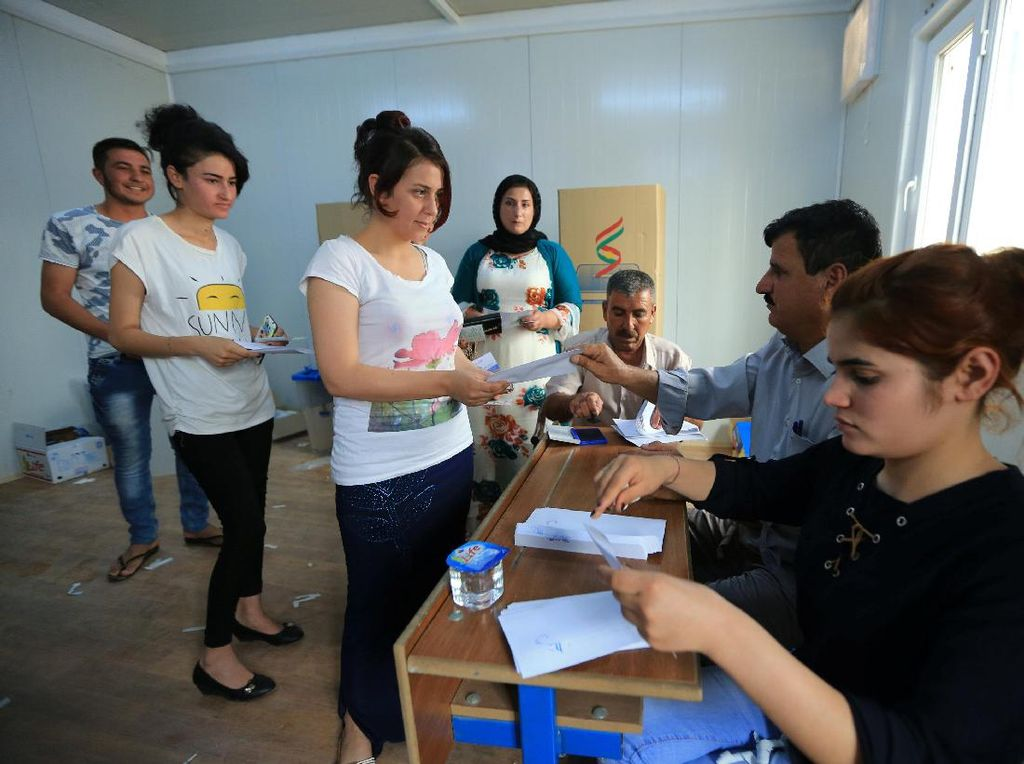 Perempuan minoritas Yazidi yang direlokasi mendatangi bilik suara di kamp pengungsian di pinggiran Duhok, Irak, 25 September 2017. (Ari Jalal/REUTERS)