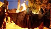 Penganut Syiah di Iran berkumpul mengelilingi api unggun setelah melumuri tubuh mereka dengan lumpur saat ritual 'Kharrah Mali' di kota Khorramabad, sekitar 470 km barat daya Teheran (1/10). ( AFP PHOTO / ATTA KENARE)