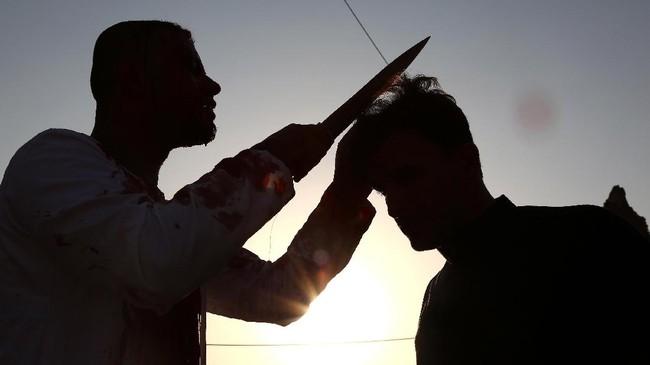 Muslim Syiah di Irak memangkas rambut di ubun kepala dengan menggunakan pisau sebagai simbol tradisi berkabung dalam peringatan Asyura. (AFP PHOTO / Haidar HAMDANI)