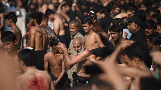 Penganut Syiah di Pakistan menyiksa diri di jalanan selama peringatan Ayura di Islamabad (30/9). Hari Asyura diperingati sebagai hari berkabung atas meninggalnya Husain bin Ali, cucu dari Nabi Muhammad pada Pertempuran Karbala tahun 61 Hijriah (680). (AFP PHOTO / FAROOQ NAEEM)