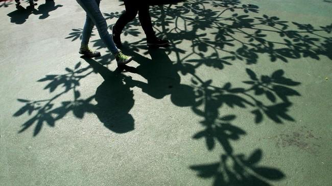 Cahaya dan bayangan menjadi kesatuan yang tak terpisahkan dalam street photography. Bayangan pohon dengan motif daunnya ditambah bayangan pengunjung berpasangan yang melintas direkam oleh Muhaimin. Tali sepatu berwarna hijau menjadi point of interest jika dilihat secara rinci. (Dok. Muhaimin A. Untung)