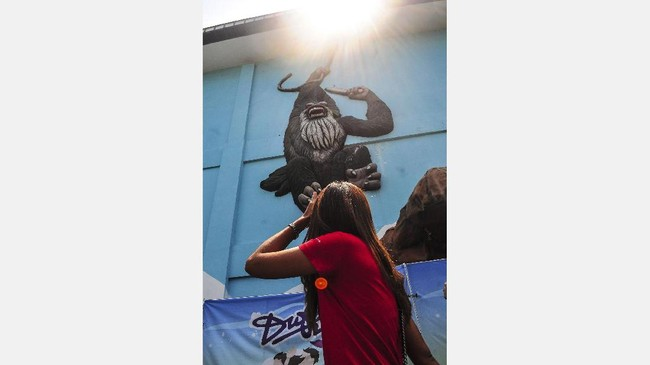 Perempuan berkaus merah berusaha menghalau sinar matahari yang menyilaukan, sementara mural gorila bergelantung seakan kakinya berusaha menangkap sang perempuan. Itulah imajinasi dari Khairuddin. Decisive moment dalam street photography menjadi nilai plus bagi pemotret. (Dok. Khairuddin Safri)