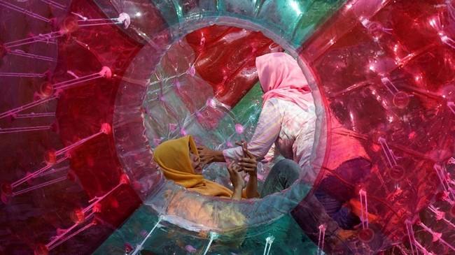Kandhi terpikat dengan wahana permainan Balon Air. Selain warna wahana yang menjadi perhatiannya, ia mencoba membingkai aktivitas dua pengunjung perempuan dengan gestur tangan yang berbeda. Pegiat street photography bisa memaksimalkan pola framing saat menemukan obyek foto. (Dok. Kandhi Dharma B.)