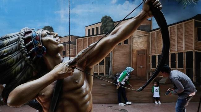 Wahana permainan Dunia Fantasi memberikan banyak pilihan untuk kegiatan street photography.Anto memilih patung sebagai foreground dan ruang framing pengunjung yang berlibur. Kecepatan menemukan momen serta ketangkasan membidik menghasilkan foto yang pas. (Dok. Anto Arianto)