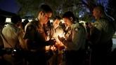 Tidak hanya warga sekitar, polisi pun ikut berbelasungkawa dan menyalakan lilin, serta berdoa. (Reuters/Chris Wattie)