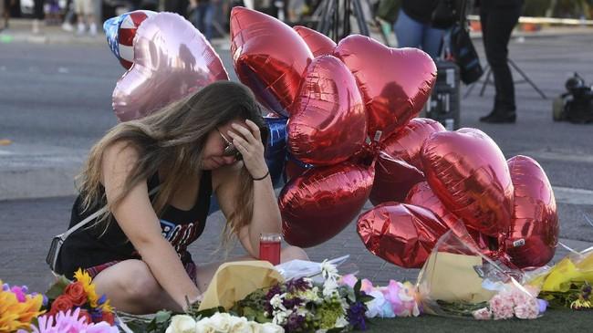 Di kerumunan orang tersebut, terlihat seorang perempuan bernama Destiny Alvers sedang menaruh bunga. Ia membantu menyelamatkan seorang temannya yang terkena tembakan saat sedang menonton festival musik Route 91 bersama. (AFP Photo/Mark Ralston)