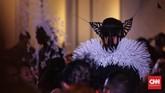 Jika topeng berwarna hitam, maka hiasan kepalanya berupa ranting, atau daun buatan berwarna putih. Begitu juga pada koleksi sebaliknya. Model yang berbusana serba putih, maka mengenakan topeng putih, tapi hiasan kepala hitam. (Foto: CNN Indonesia/Hesti Rika)