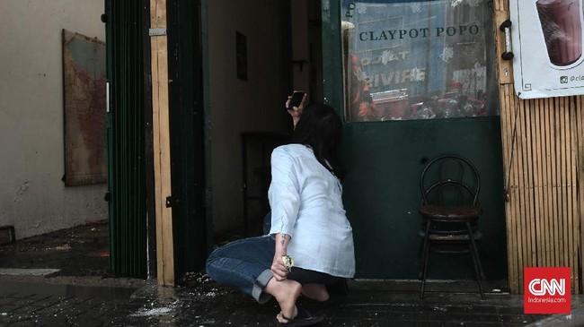 Pemilik cafe yang diduga mengalami arus pendek listrik tengah mengambil gambar keadaan cafe di salah satu pertokoan di Jalan Sabang, Jakarta Pusat, Minggu (8/10). Kebakaran tersebut diduga disebabkan oleh arus pendek listrik dari salah satu cafe yang ikut terbakar. (CNN Indonesia/Andry Novelino).
