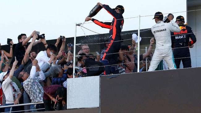 Lewis Hamilton, Max Verstappen, dan Daniel Ricciardo menyemprotkan sampanye kepada para penonton dari atas podium GP Jepang. (REUTERS/Toru Hanai)
