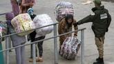 <p>Para perempuan ini menunggu instruksi untuk menyerahkan barang yang diangkut mereka. Mereka kemudian membawa barang angkut yang telah dikemas dalam bentuk tas persegiyangdiikat dengan tali, kemudian mereka mengambil tiket dengan jumlah bayaran yang mereka terima setelah pengiriman. (AFP PHOTO/FADEL SENNA)</p>