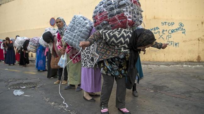 <p>Para buruh angkut perempuan ini biasanya berkumpul dalam sebuah antrian melalui persimpangan perbatasan di sebuah bukit yang menghadap ke Mediterania antara kota Fnideq di Maroko dan pelabuhan Ceuta, Spanyol. (AFP PHOTO/FADEL SENNA)</p>