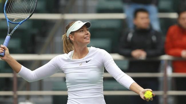 <p>Maria Sharapova merayakan kemenangan atas Irina-Camelia Begu dengan memberikan bola ke arah penonton di tribune usai pertandingan. (AFP PHOTO / STR)</p>