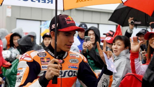 Pemuncak klasemen sementara Marc Marquez berjalan menuju paddock Repsol Honda jelang latihan bebas pertama MotoGP Jepang di Sirkuit Motegi, Jumat (13/10). (AFP PHOTO/Toshifumi KITAMURA)