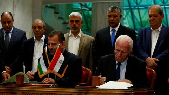 Kepala delegasi Hamas Saleh Arouri dan pemimpin Fatah Azzam Ahmad menandatangani kesepakatan rekonsiliasi di Kairo, Mesir, 12 Oktober 2017. (REUTERS / Amr Abdallah Dalsh).