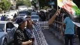 Seorang polisi berpose untuk wefie dengan seorang pria yang mmengibarkan bendera Palestina saat orang-orang berkumpul di Kota Gaza untuk merayakan rekonsiliasi Hamas dan Fatah. (AFP PHOTO / MAHMUD HAMS).