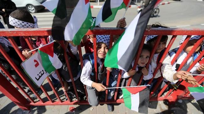 Anak-anak memegang bendera Palestina dalam perayaan menyambut rekonsiliasi Hamasdengan Fatah,di Jalur Gaza.(REUTERS / Ibraheem Abu Mustafa).