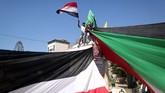 Warga Palestina mengibarkan bendera Mesir dan Palestina saat mereka berkumpul di Kota Gaza untuk merayakanrekonsiliasi Hamas dan Fatah. (AFP PHOTO / MAHMUD HAMS).