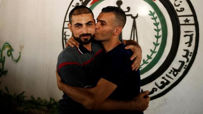 Seorang anggota gerakan Fatah dipeluk dan dicium saat dibebaskan dari penjara yang dikelola Hamas sebagai bagian dari upaya rekonsiliasiHamas-Fatah. (REUTERS / Mohammed Salem).